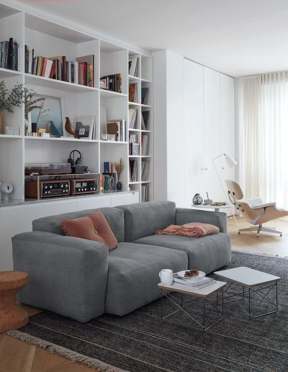 a contemporary living room with built-in storage units, a grey low sofa, a couple of coffee tables and a white lounger