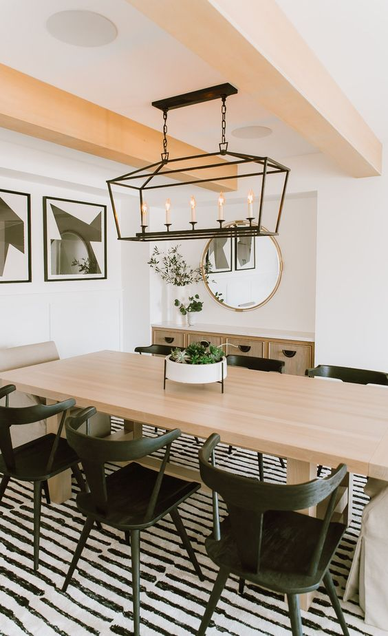 a contrasting dining room with blonde wood beams, a blonde wood table and black chairs plus a gorgeous vintage-inspired black lamp