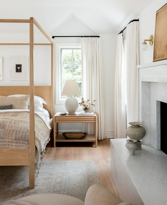 a cool and serene bedroom in neutrals, with a non-working fireplace, a blonde wood canopy bed and a matching nightstand is chic