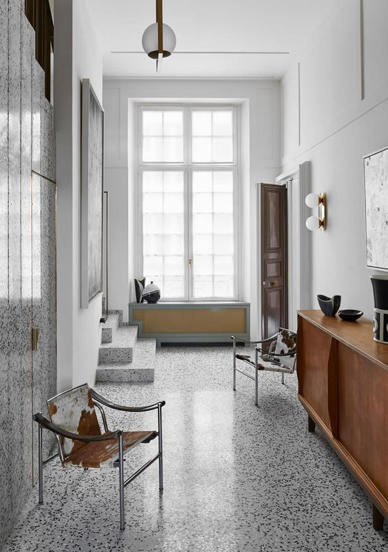 a cool mid-century modern entryway with a terrazzo floor and a wlal, leather and metal chairs and a chic wooden credenza