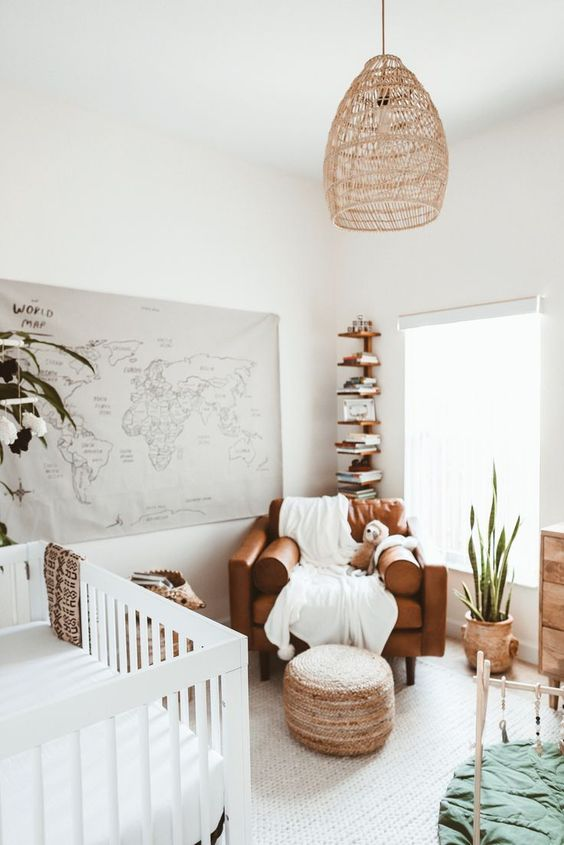 a cool neutral nursery with a white crib, a brown chair, a stained shelf in the corner, a woven lamp and a map of the world