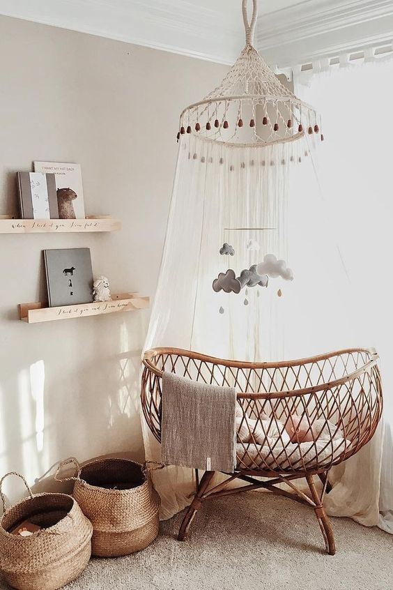 a cool neutral nursery with floating shelves, a rattan crib, a canopy and a mobile and baskets for storage
