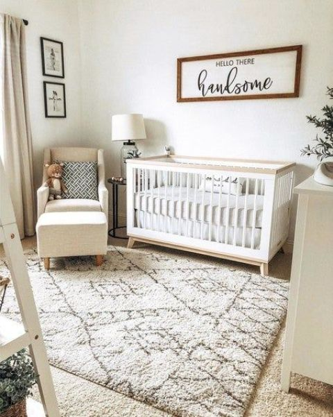 a cozy neutral nursery with a modern crib, a cozy chair with a footrest, some artworks and pretty neutral textiles