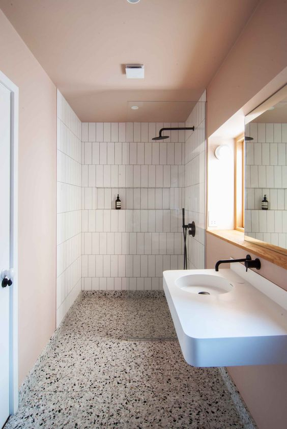 a cozy pastel bathroom with pink walls and a ceiling, with white skinny tils and a grey terrazzo floor plus a white wall mounted sink