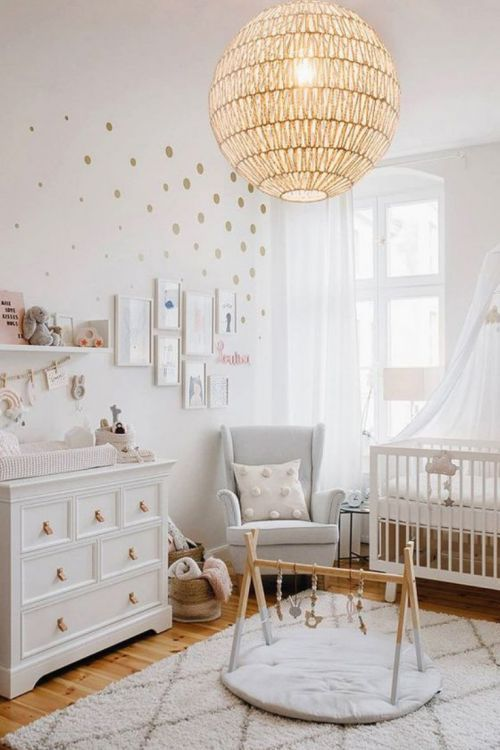 a cute and lovely neutral nursery with white and grey furniture, layered rugs, a sphere lamp and polka dot touches