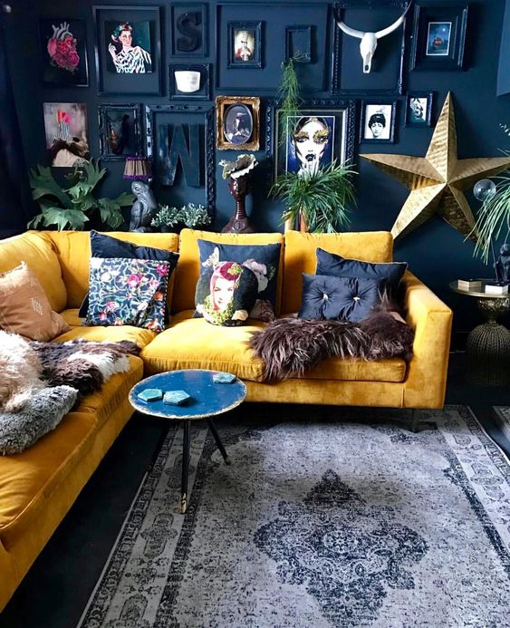 a dramatic living room with a navy accent wall, a bold gallery wall, a yellow sectional and bright pillows plus a round table