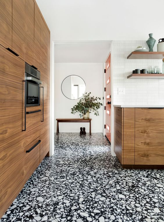 a gorgeous black and white terrazzo floor from entryway to the kitchen connects these spaces and adds interest to them