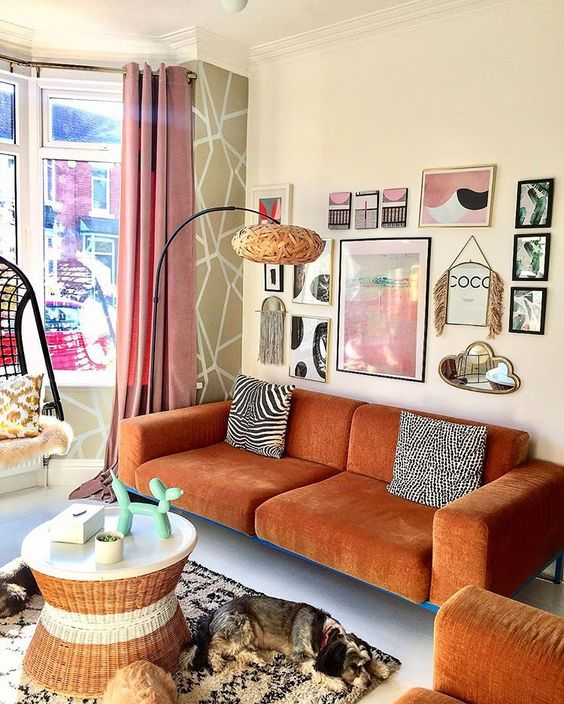 a gorgeous eclectic living room with a rust-colored sofa and a matching chair, a round table, a pretty gallery wall and a floor lamp