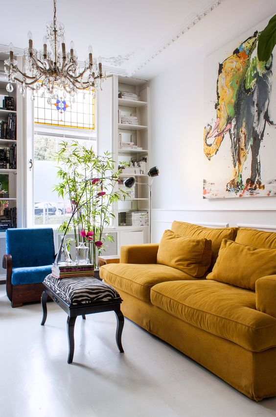 a gorgeous maximalist living room with a mustard sofa, a blue chair, potted plants, a refined chandelier and a bold artwork