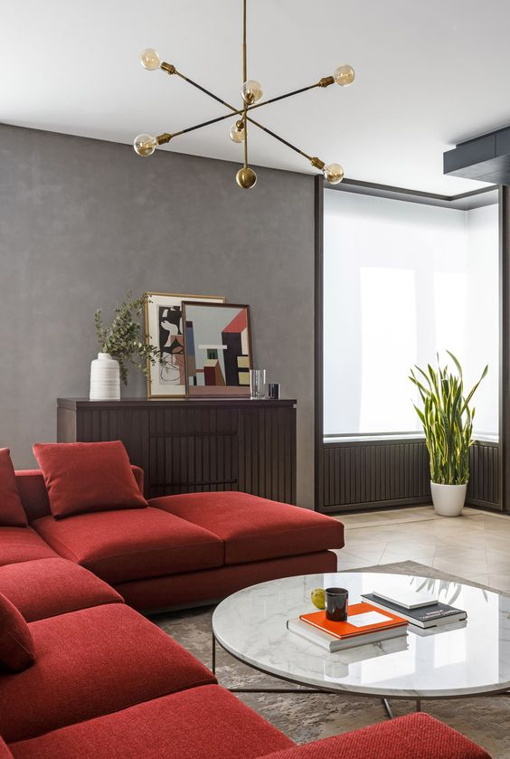 a laconic modern living room with grey walls, a depe red sectional, a wooden storage unit and a low round table