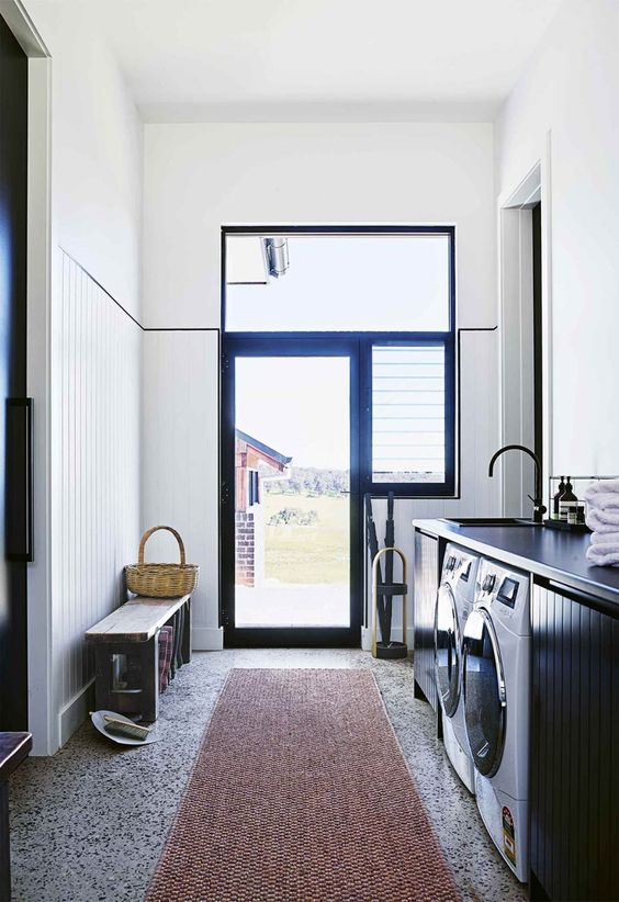 a laundry room done in black and white, with grey terrazzo tiles on the floor that add a cool and fun touch