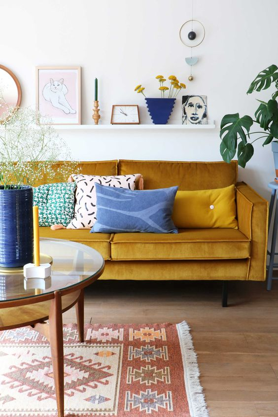 a lively living room with a mustard sofa, a round table, a ledge gallery wall and touches of blue for a contrast