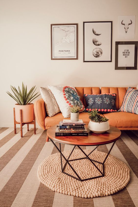 a lovely boho living room with an orange leather sofa, a wooden bead rug and a geo table, a monochromatic gallery wall