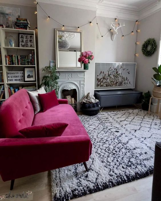 a lovely contemporary neutral living room with built-in shelves, a non-working fireplace, a hot pink loveseat, potted plants and a cool gallery wall