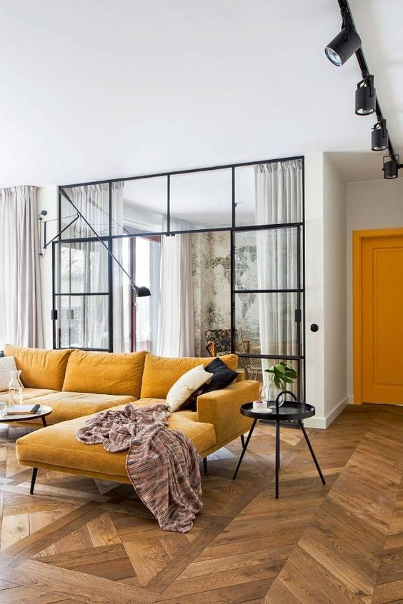a lovely contemporary space with a warm yellow sectional, a black able and some black and white pillows