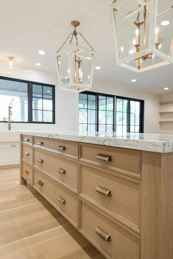 a lovely kitchen with a blonde wood floor and a large kitchen island with storage, elegant faceted pendant lamps