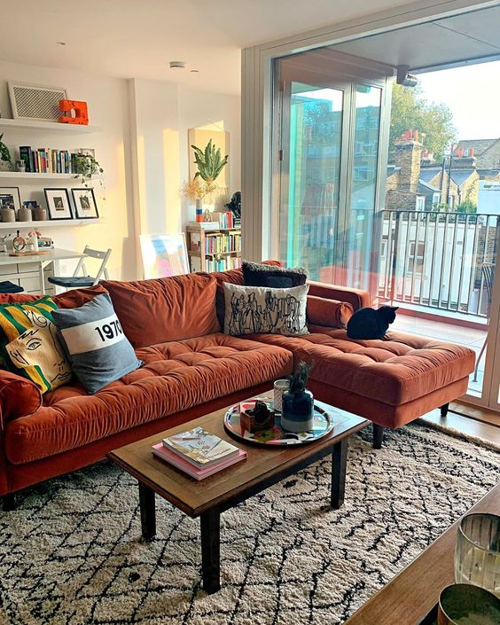 a lovely living room with a rust-colored sectional, a low table, floating shelves and potted plants here and there