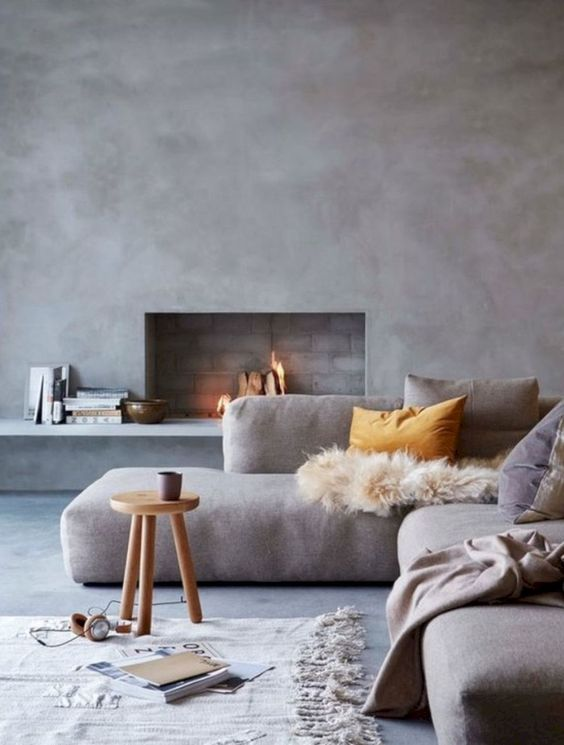 a lovely minimalist living room with concrete walls, a built-in fireplace, a low grey sofa, a roudn stool and various textiles