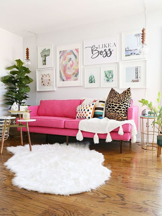 a lovely modern living room done in neutrals, witha pink sofa, an airy gallery wall, white textiles, potted plants and some tables