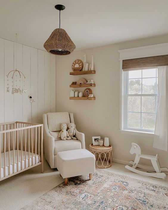 a lovely modern neutral nursery with floating shelves, a light stained crib, a white chair and a footrest, a rattan pendant lamp and a printed rug