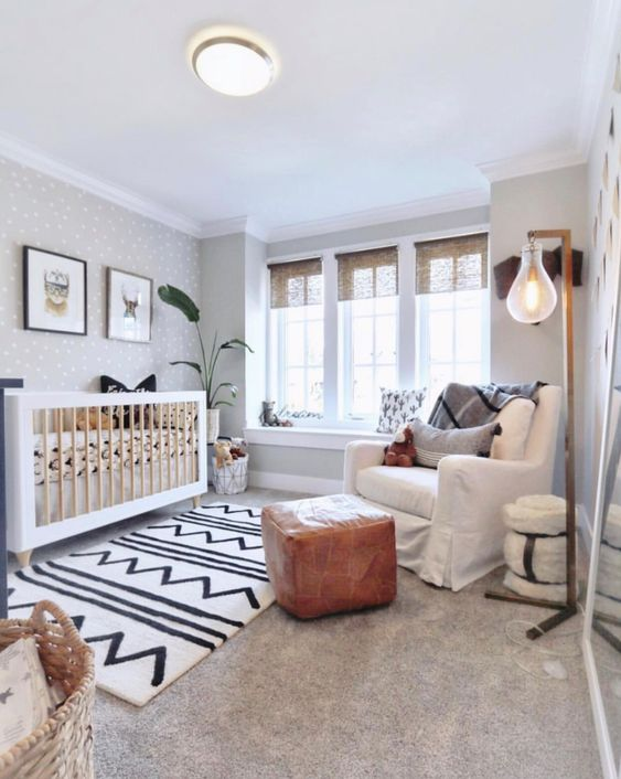a lovely neutral nursery with a large crib, a white chair and a leather pouf, layered rugs, a basket and a floor lamp plus a grey polka dot wall