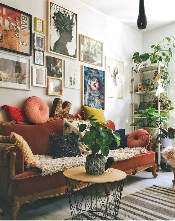 a maximalist living room with a colorful gallery wlal, a rust-colored vintage sofa, a round table and potted plants