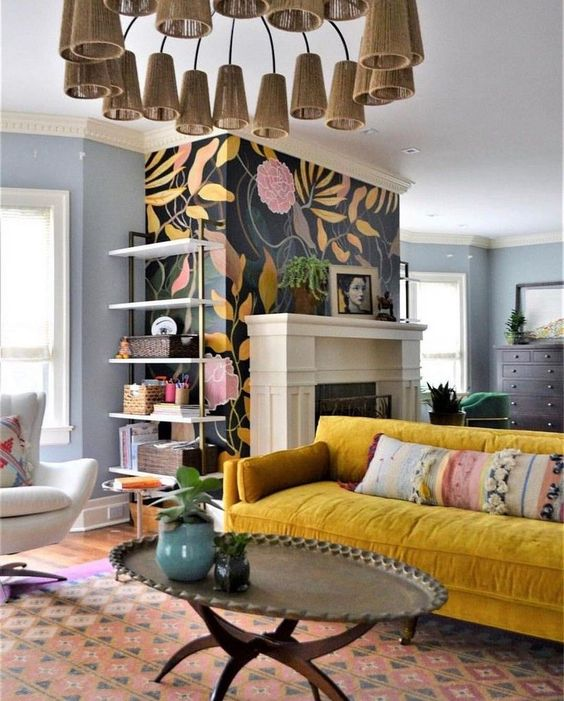a maximalist living room with a fireplace, a floral wall, a msutard sofa, a low metal table and a cone chandelier