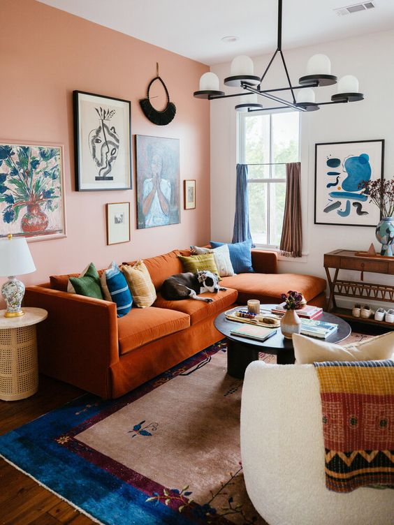 a maximalist living room with a pink accent wall, an orange sofa with colorful pillows, neutral furniture and bold textiles plus colorful curtains