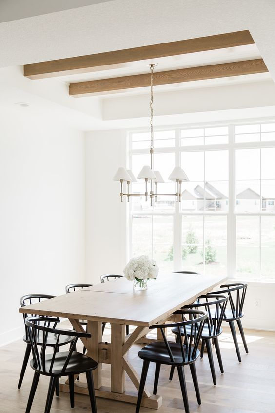 a mid-century modern dining room with a blonde wood trestle table and beams, black chairs and a vintage chandelier