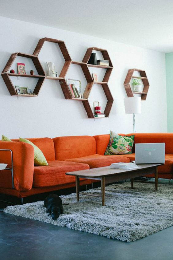 a mid-century modern living room with an orange sofa, hexagon shelves, a low table and colorful pillows is welcoming