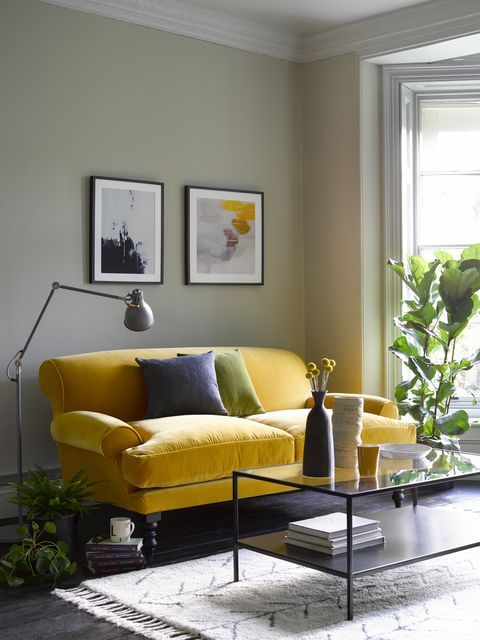a mid century modern living room with grey walls, a lemon yellow vintage sofa, a small gallery wall, a black low table and potted plants