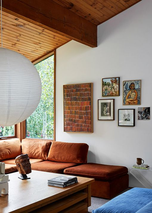 a mid century modern space with a large rust colored sectional, a low wooden table and a blue pouf plus a whimsy gallery wall