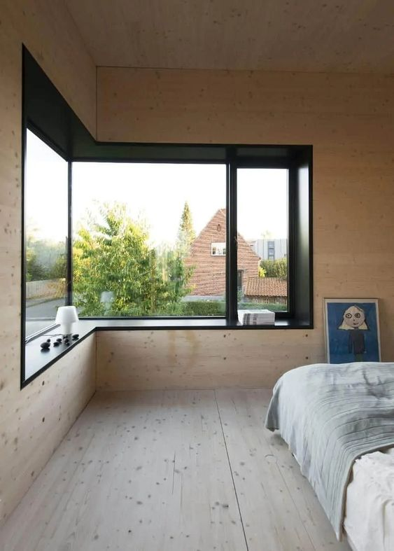 a minimalist bedroom clad with blonde wood, with a lovely view, contemporary furniture and a windowsill seat