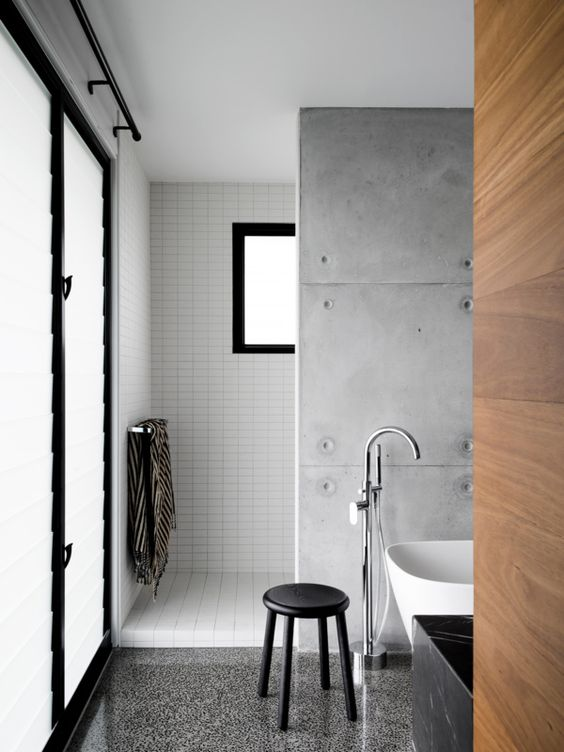 a minimalist industrial bathroom with white skinny tiles, a concrete tile wall and a grey terrazzo floor plus a white bathtub