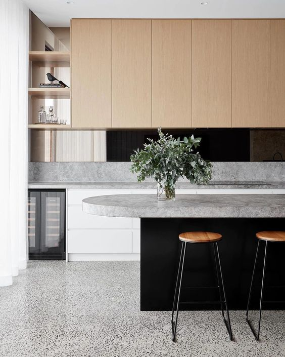 a minimalist kitchen with a grey terrazzo floor, sleek cabinetry and grey stone countertops that add interest just like the floors