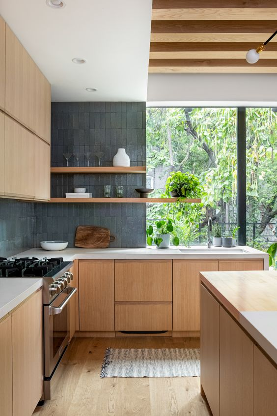 a minimalist kitchen with blonde wood cabinetry, graphite grey tiles, white stone countertops and lvoely views