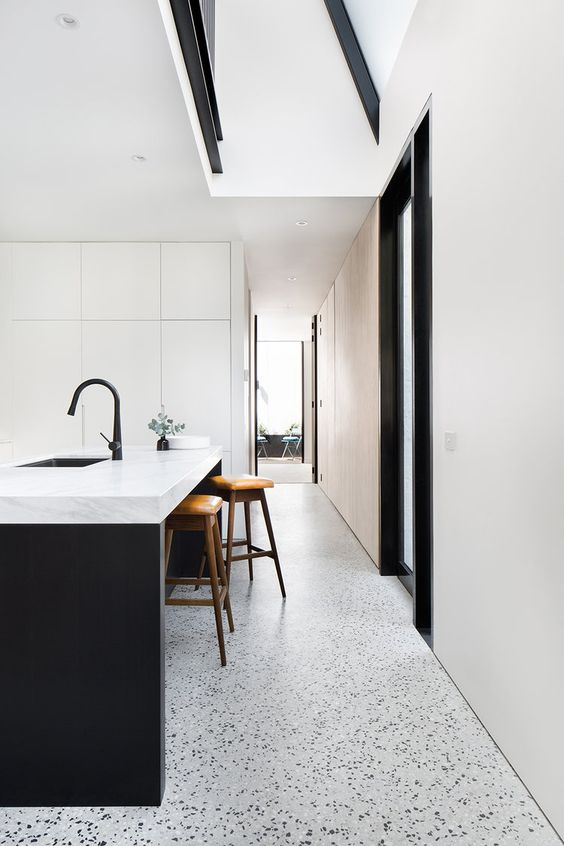 a minimalist kitchen with sleek white cabinetry, a black kitchen island, terrazzo floors and black fixtures