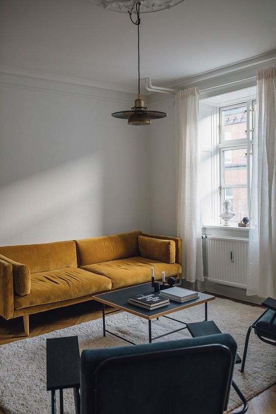 a minimalist living room with a mustard sofa, teal chairs, a low coffee table and a retro pendant lamp for a twist