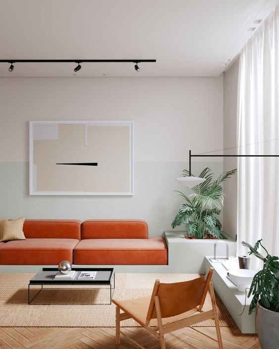 a minimalist living room with an orange velvet sofa, a low table and a leather chair plus potted plants and an abstract artwork