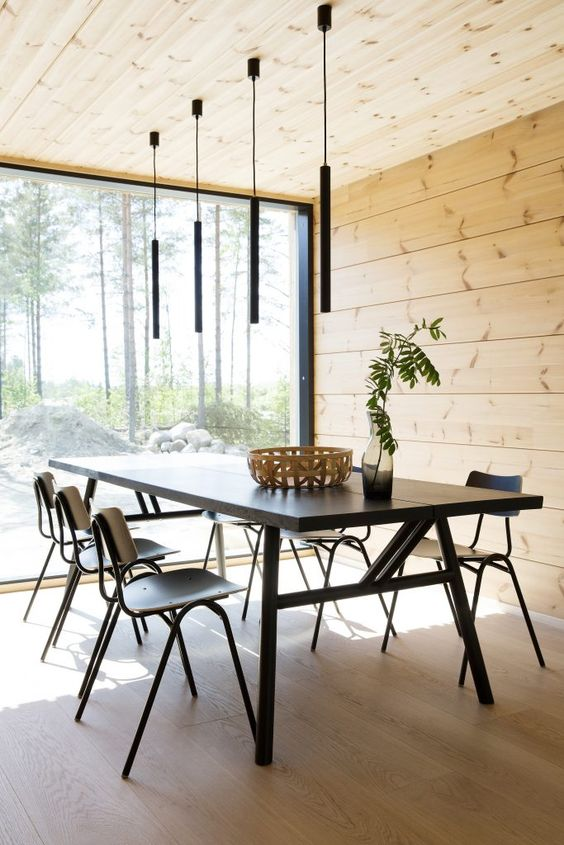 a modern dining room clad with blonde wood all over, with black furniture and lamps and a gorgeous natural view