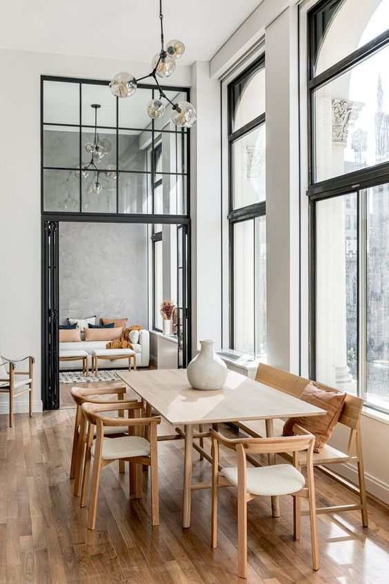 a modern dining space with a blonde wood dining set, a rich stained floor and a retro pendant lamp is beautiful and cool