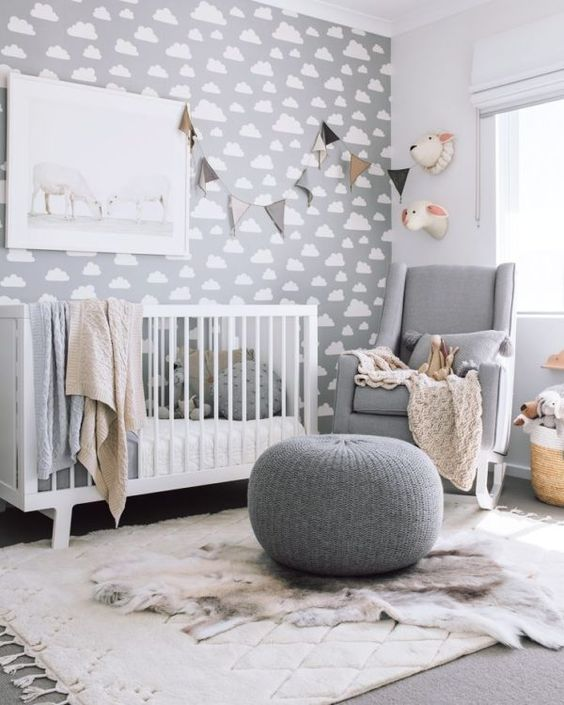 a modern grey nursery with a cloud print wlal, a grey rocker and a white crib, a grey pouf, a bunting and faux taxidermy for a fun touch