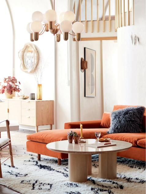a modern living room done in neutrals, with a rust colored sectional, a low round table and a mid century modern chandelier to light up the space