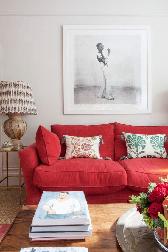 a modern living room with a bold red sofa, printed pillows, a statement artwork, a printed lamp and stacks of books
