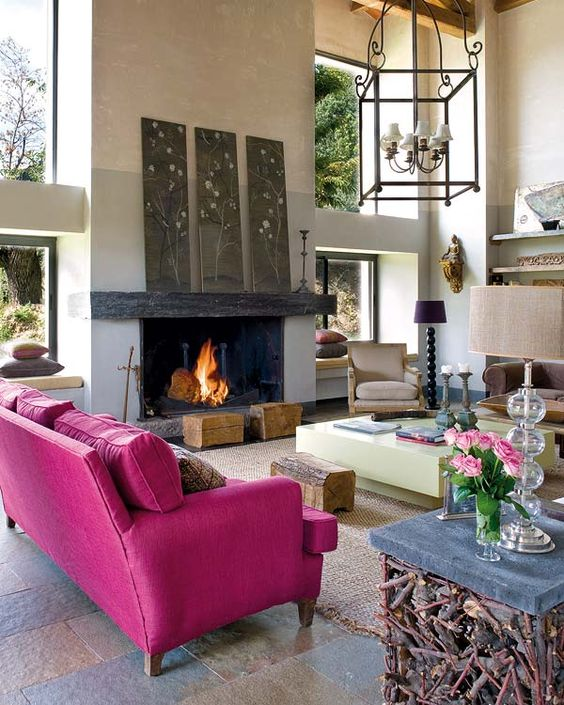 a modern living room with a fireplace, a hot pink sofa, floral artworks, a creative table with wood, tree stumps and catchy lamps