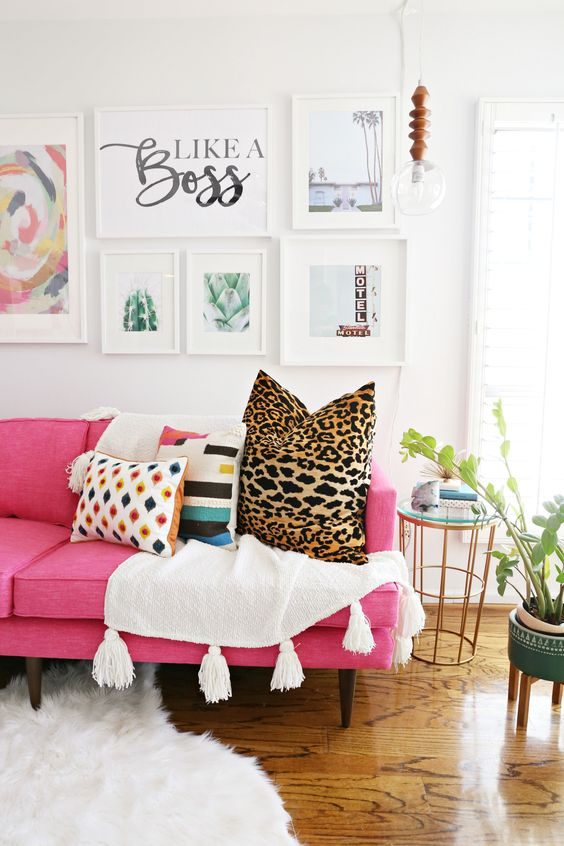 a modern living room with a hot pink sofa, printed pillows, a chic gallery wall, a pendant bulb and potted plants