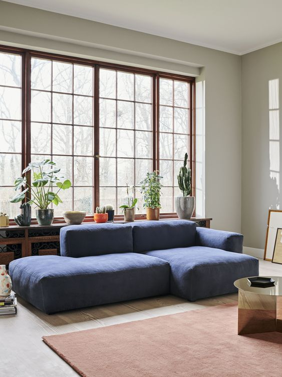 a modern living room with a low blue sofa, a metallic table, a rust rug and a whole collection of potted plants on the windowsill
