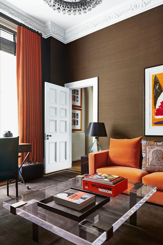 a modern living room with an orange sofa, a low acrylic table, a desk and a leather chair plus a crystal chandelier
