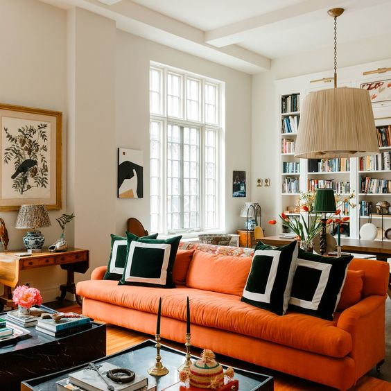 a modern living room with an orange sofa, a pendant lamp, graphic pillows, some coffee tables and lovely artworks