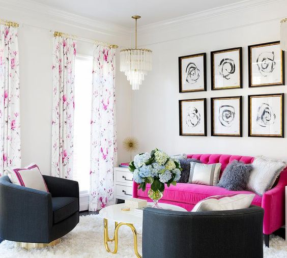 a modern living room with black chairs, a hot pink sofa, a grid gallery wall, a chic chandelier and floral curtains
